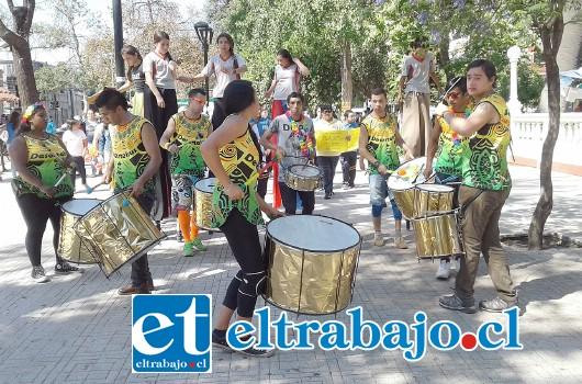 Una agrupación de jóvenes tocan en la batucada mientras otros integrantes de Zancos de la Escuela José Manso de Velasco hacen de las suyas en sus zancos.