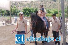La pequeña Piera junto a su terapeuta sobre 'Bernardita', una de las yeguas destinadas a 'monta gemela', terapia que puede durar aproximadamente 30 minutos y que necesita además dos personas como apoyos laterales y un tirador del caballo.