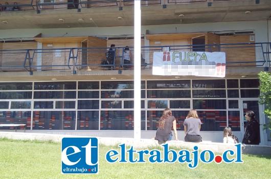En el patio central del campus San Felipe de la Upla, pancartas piden la salida del docente.