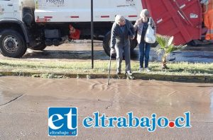 Una pareja de adultos mayores apoyándose en su bastón para poder cruzar debido al verdadero río que había en avenida Miraflores.