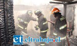 Bomberos en plena acción remojando el terreno tras controlar el incendio.