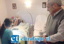El alcalde Pedro Caballería observa a la funcionaria atendiendo a la paciente postrada en su propia casa, una gran innovación pionera en el valle de Aconcagua.