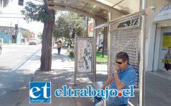 Un vecino descansa en uno de los paraderos de la calle Santo Domingo que debiera cambiar el sentido del tránsito.