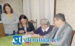 Acá vemos a Raquel González Otárola estampando su firma en el documento que da por terminado su problema.