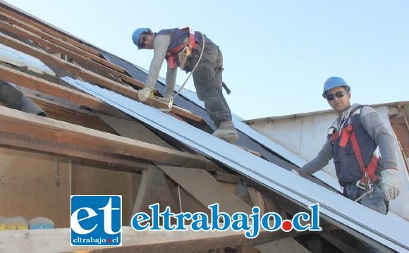 EN PLENA ACCIÓN.- Las cámaras de Diario El Trabajo registran justo el momento en que estos dos obreros hacen las labores en la techumbre de don Anselmo González.