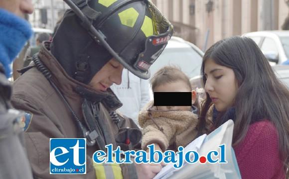 RESCATADO.- La madre del bebé recuperó en pocos minutos a su guagua, mientras que este bombero le tomaba sus datos.