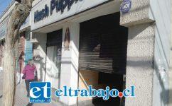 Cortina a medio abrir de la tienda de zapatos Hush Puppies ubicada en calle Salinas, a pasos de la plaza de armas.
