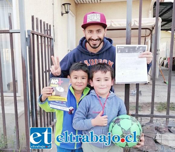 Un adulto con dos niños orgullosos y sonriendo muestran el formulario que los acredita como socio cooperador de bomberos.