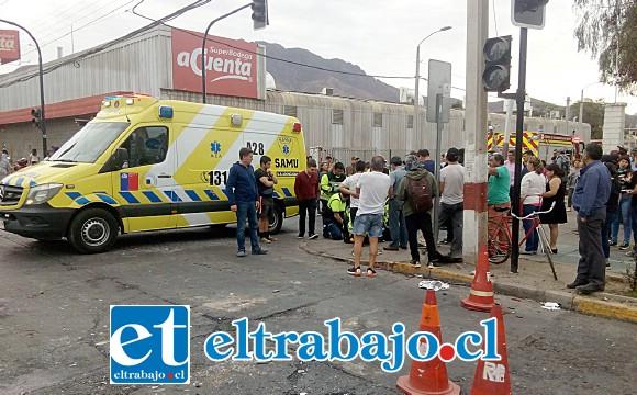 Personal del SAMU asiste a los heridos en el lugar del suceso, en medio de un numeroso grupo de curiosos que observaban la impactante escena.