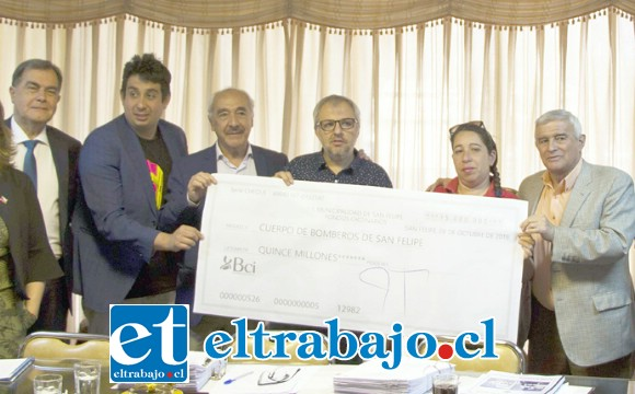 Alcalde y concejales entregando un gigantesco  cheque a la institución de los 'Caballeros del Fuego'.