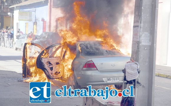 El momento exacto en que los delincuentes huyeron con el millonario botín, incendiando este vehículo en el frontis de la sucursal Servi Estado en calle Santo Domingo de San Felipe.
