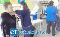 Una enfermera aplica la vacuna contra la influenza a una adulto mayor.
