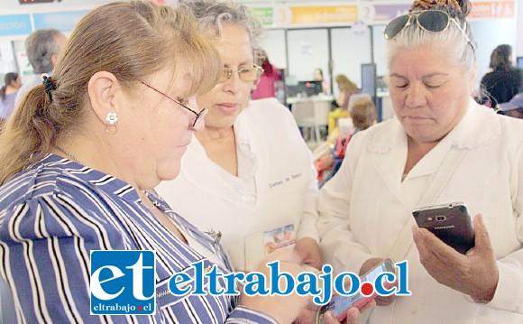 Damas de Blanco y una integrante del Consejo de Desarrollo Local del hospital, revisan las funcionalidades de la nueva aplicación.