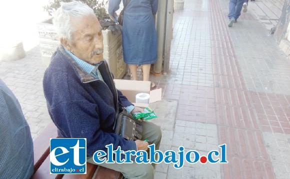Emilio Tapia sentado en calle Prat con el producto que vende en la mano, en este caso gomitas de eucaliptus.