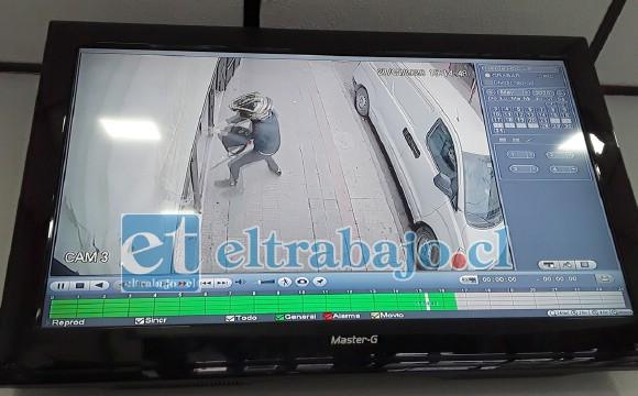 En la imagen captada por las cámaras de vigilancia del local, se aprecia al delincuente en plena faena intentando romper el vidrio de la mampara.