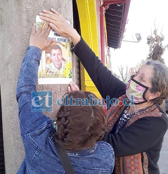 En un poste colocando el retrato de Mauricio pidiendo justicia.