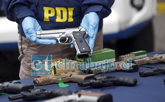 Una de las tantas pistolas incautadas muestra el funcionario de la PDI.