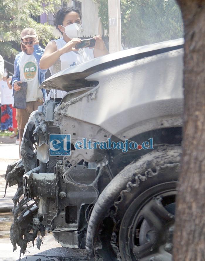 PARA NO CREERLO.- La directora de Fundación María Ayuda, Carol Cisternas, saca fotografías a su auto destruido.