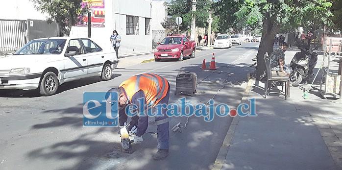 Un funcionario con un esmeril eléctrico corta los pernos que unían las tachas al cemento en calle Merced.
