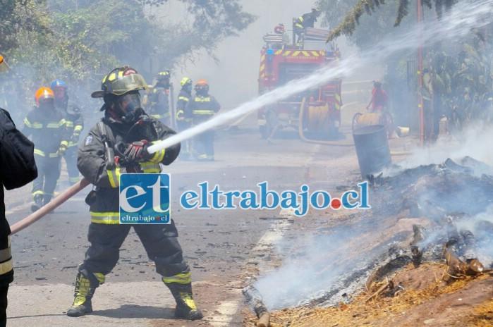 BOMBEROS EN ACCIÓN.- Los bomberos lograron evitar que este incendio consumiera más viviendas del sector.