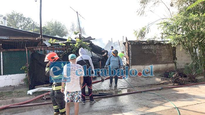 Personal de bomberos efectuando remojo una vez terminado el incendio que destruyó dos viviendas.