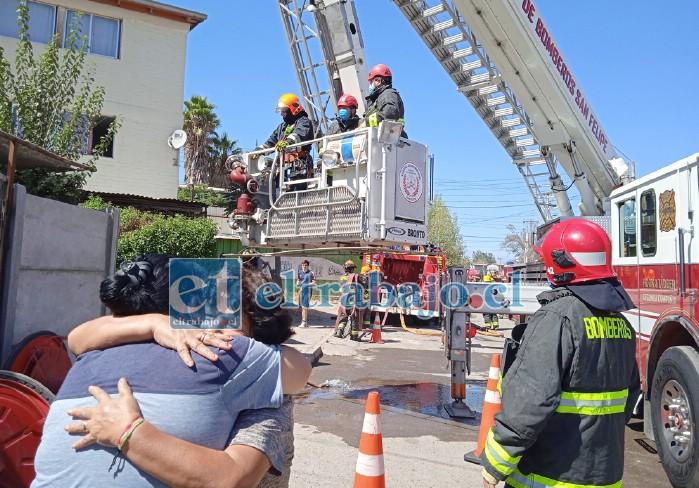 DRAMA EN LA DEPARTAMENTAL.- Personal de Bomberos en el lugar debieron usar la unidad MX-2 a escala, mientras una mujer abraza a su vecina, demostrando la pena por la situación.